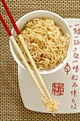 Asian noodle dish in a bowl with chopsticks