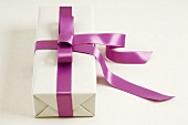 Gift in white wrapping paper with purple ribbon