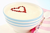 Redcurrants forming a heart in a bowl of yoghurt