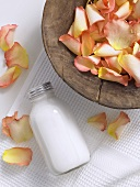 Rose petals in a wooden dish, small bottle of body lotion