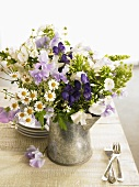 Jug of summer flowers: sweet peas, chamomile, monkshood, phlox