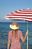 Frau mit Hut und rot-weißem Sonnenschirm am Meer