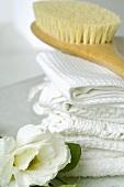 Handtücher und Massagebürste dekoriert mit Lisianthusblumen