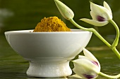 Bowl of turmeric and orchid