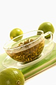 A cup of green tea with limes