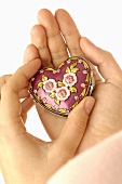 Hands holding heart-shaped box