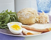 Ham with boiled egg, rocket and bread roll