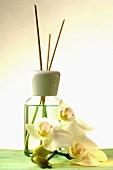 Duftflakon mit Aromastäbchen und Orchideenblüte