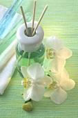 Duftlampe mit Aromastäbchen und Orchideenblüten