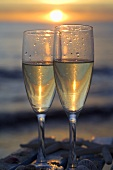 Two glasses of sparkling wine by the sea with setting sun