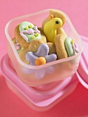 Decorated Easter biscuits in plastic food storage box