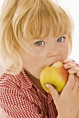 Little girl eating an organic apple