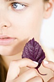 Young woman with a purple basil leaf