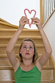Girl holding candy canes together to form a heart