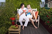 Couple sitting on a bench out of doors & eating watermelon