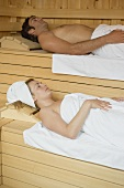 Man and woman lying in a sauna