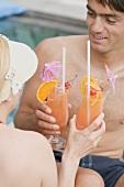Frau und Mann mit Planters Punch am Pool