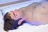Young man in tanning goggles lying on a tanning bed