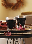 Mulled wine in two glasses and maple leaves on tray