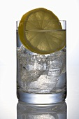 A glass of mineral water with ice cubes and slice of lemon