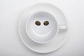 Eine Kaffeetasse mit zwei Kaffeebohnen als lächelndes Gesicht