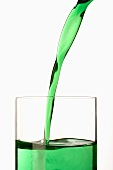 Pouring mint syrup into a glass