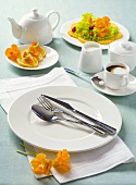 White place-setting with orange slices and coffee