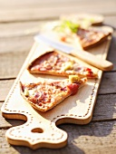 Slices of pizza on chopping board