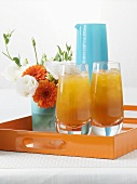 Apricot juice and small posy of flowers on tray