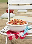 Tomato and bread salad on a chair on the beach