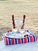 Pink Diamond cocktail with raspberry skewers on the beach