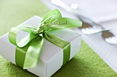 Small gift with green ribbon beside forks