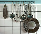 Various kitchen utensils hanging on a bar