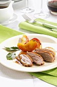 Roast goose breast with peach wedges