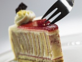 A piece of raspberry marzipan cake with cake fork