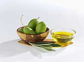 Green olives, olive leaves and olive oil