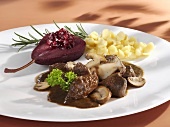 Venison ragout with mushrooms and red wine pear