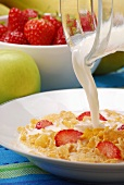 Pouring milk over cornflakes and strawberries