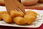 Potato croquettes with wooden fork (close-up)