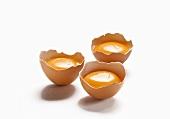 Drei aufgeschlagene Eier in Eierschalen