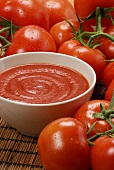 Home-made tomato sauce in bowl and fresh tomatoes
