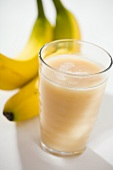 Glass of banana juice, two bananas behind