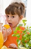 Mädchen leckt an Zitrone, daneben Krug mit Zitronenlimonade