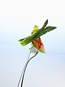 Charentais melon, chilli and green asparagus on a fork
