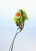 Lettuce, asparagus, quail's egg and red caviar on a fork