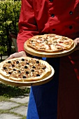 Chef carrying two pizzas on wooden boards