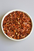 Dried chilli flakes in small white bowl