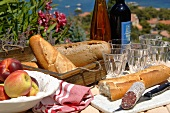 Baguette, salami, fruit and wine on laid garden table