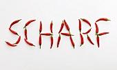 Schriftzug SCHARF aus roten Chilischoten