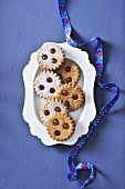 Linzer Augen (nutty shortcrust jam sandwich biscuits with holes on top) on a serving plate
